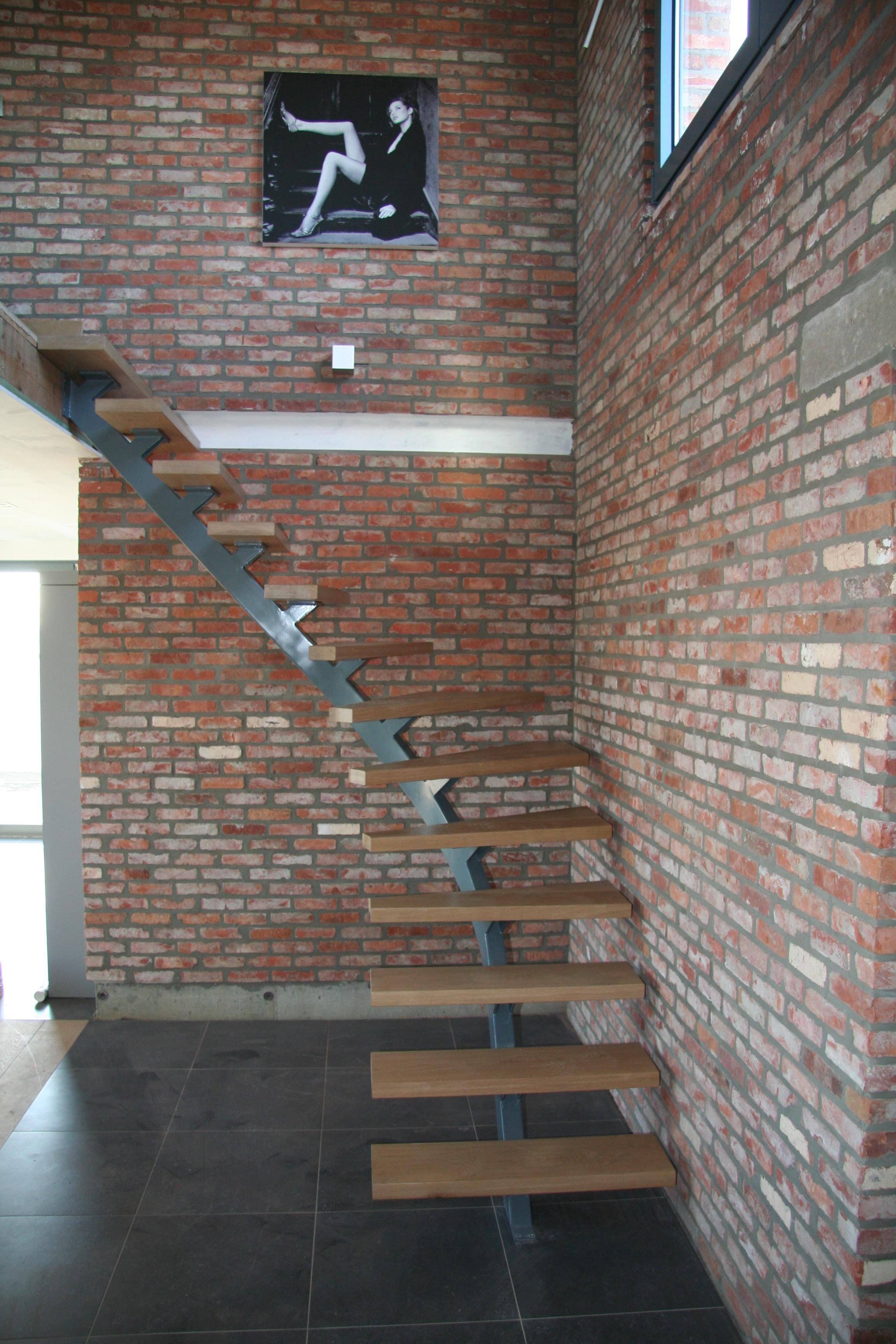 metalen wenteltrap met houten treden naar mezzanine in loft